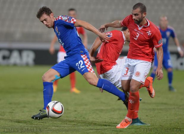 Croatia's Josip Pivaric (left) tries to break free from Malta's Joseph Zerafa during their UEFA European Championship Qualifying match against Malta at the National Stadium in Ta'Qali on October 13. Photo: Matthew Mirabelli