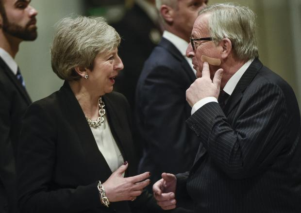 European Commission President Jean-Claude Juncker gestures as he welcomes British Prime Minister Theresa May after her arrival at the EU headquarters.