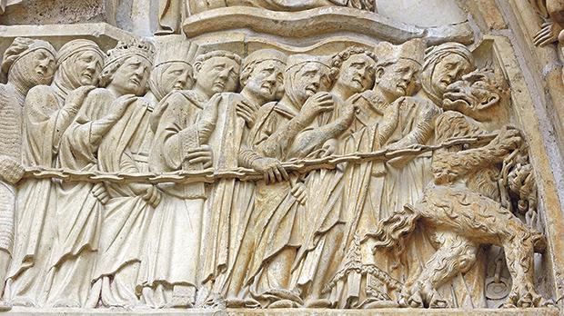 Architectural details of lost souls being led into hell on the façade of Notre Dame' Cathedral in Paris.