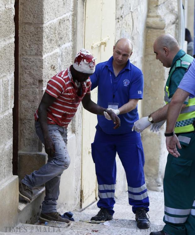 A 19-year-old Sudanese man is tended to by paramedics after being grievously injured in a fight with a Libyan man in Valletta on June 4. The Sudanese man was pushed through the glass door of a hotel and rushed to hospital with serious head wounds. Photo: Darrin Zammit Lupi
