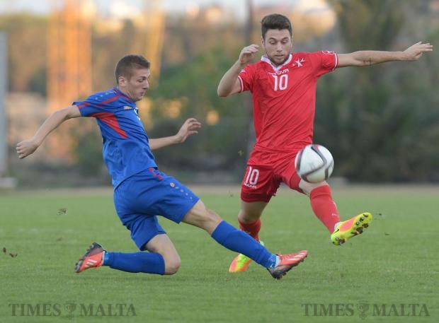 Malta's Johann Bezzina (right) makes his way past Moldova's Dinu Graur during their UEFA U21 Championship group match at the Hibernians Stadium in Corradino on October 11. Photo: Matthew Mirabelli