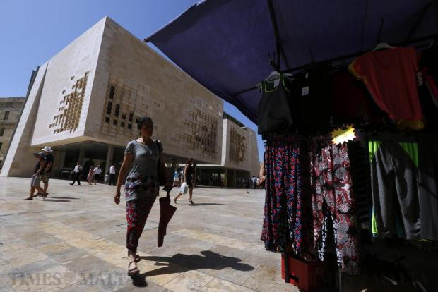 A woman looks at bargain clothing at the Valletta flea market, better known as the Monti, across the street from Renzo Piano's landmark Parliament building in Valletta on August 1. Photo: Darrin Zammit Lupi