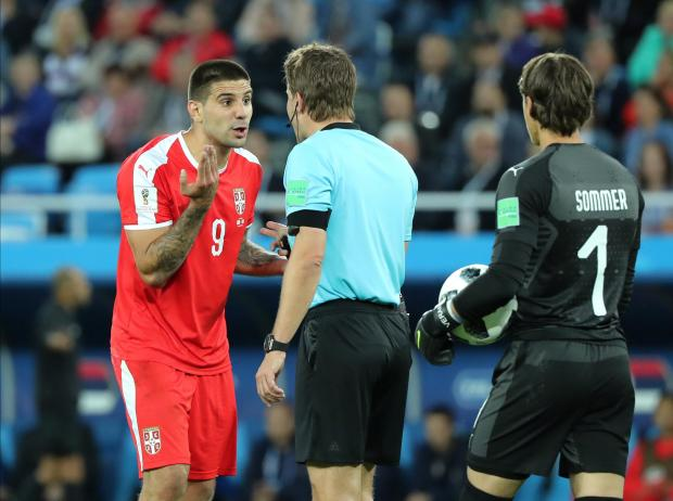 Aleksandar Mitrovic protests with the referee after he was not awarded a penalty against Switzerland.