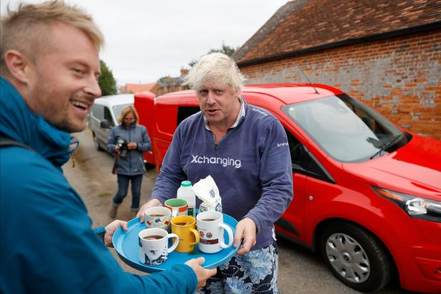 Britain's former Foreign Secretary Boris Johnson offers cups of tea to journalists outside his home near Thame in Oxfordshire.