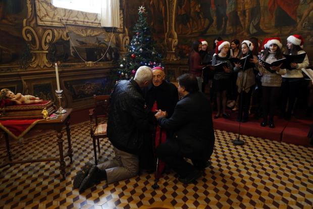 People kneel and crouch as they exchange greetings with Archbishop Emeritus Joseph Mercieca at the Curia in in Floriana on December 28. Photo: Darrin Zammit Lupi
