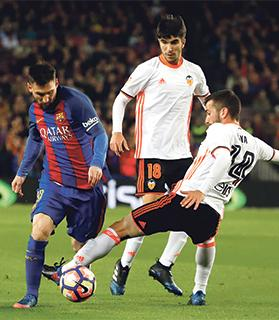 Lionel Messi tries to avoid the challenge of Jose Luis Gaya, of Valencia.