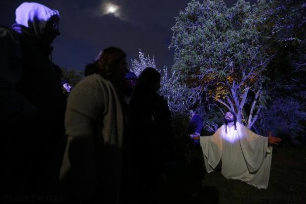 "Audience members watch an actor portraying Jesus Christ (right) during the interactive street-theatre performance of ""Il-Mixja"" in the grounds of Mount Carmel Mental Hospital in Attard on March 31. Photo: Darrin Zammit Lupi"
