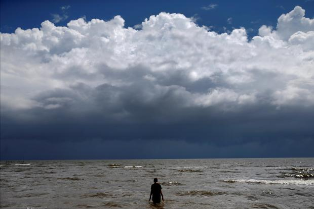 A teenager wades in the ocean as Tropical Storm Gordon approaches Waveland, Mississippi. Photo: Reuters/Jonathan Bachman