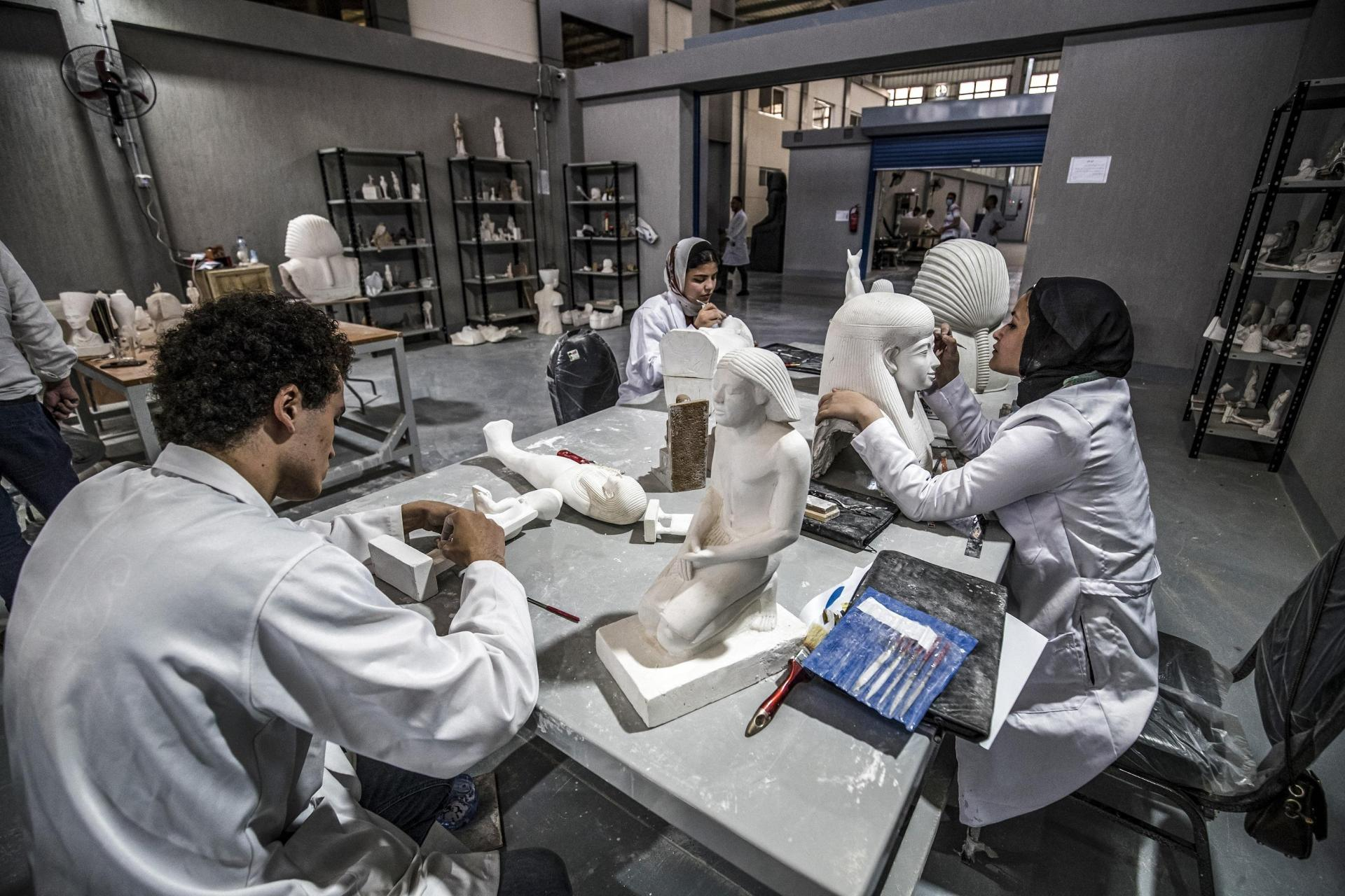 Technicians paint replicas of an Ancient Egyptian statues being fabricated at the Egyptian government's Konouz (Treasures) factory reproducing replicas of Ancient Egyptian items, at el-Obour city, east of the capital Cairo on May 17, 2021.