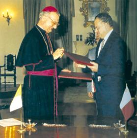 Ugo Mifsud Bonnici exchanging documents with Papal Nuncio Mgr Pier Luigi Celata following the Church-State agreement about acquisition of Church property and state subsidies to Church schools.