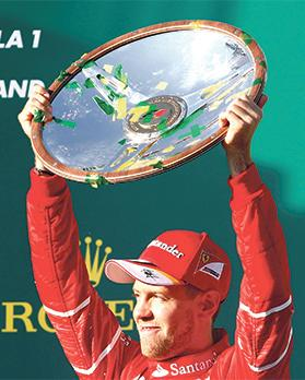 Sebastian Vettel lifts his trophy on the winners' podium in Melbourne, on Sunday.