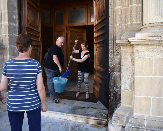 Members of the community help out in cleaning a church door after it was set alight by an arsonist on August 29. Photo: Mark Zammit Cordina