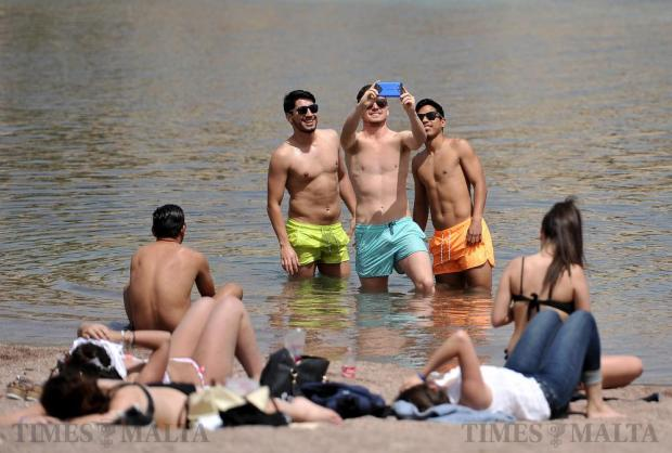 Three young men take a group selfie on the sand of St George's Bay on April 13. Photo: Chris Sant Fournier