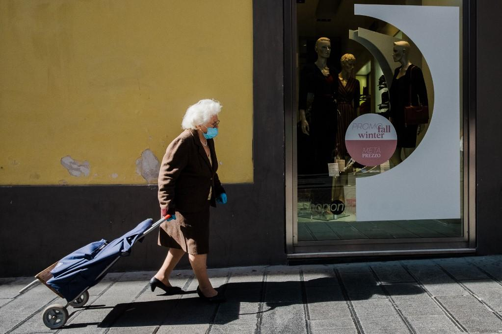 An elderly woman wearing a mask walks in downtown Naples. Photo: AFP