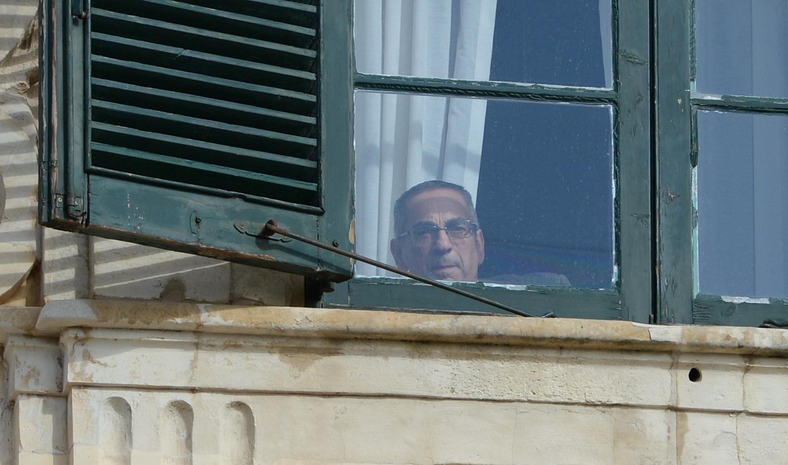 Minister Joe Mizzi looks on from the Cabinet room onto the movements in Castille Square. Photo: Matthew Mirabelli