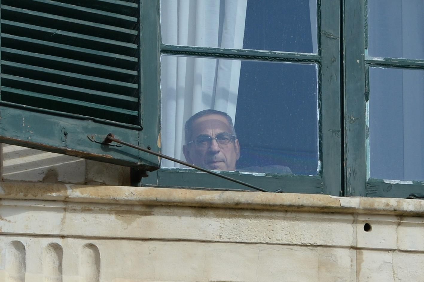 Minister Joe Mizzi looks out of a window at the Auberge de Castille. Photo: Matthew Mirabelli