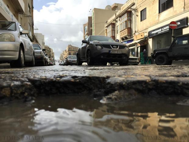 "A waterlogged pothole is seen near parked cars on January 24. Remedying the perpetual abundance of potholes is ""hopeless"" without a massive injection of funds, traffic expert. Hugh Arnett told Times of Malta. Photo: Jason Borg"