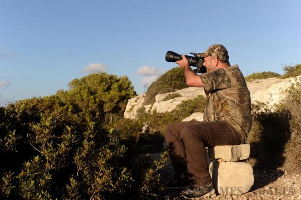 A hunter who developed a passion for photography takes a shot with his camera at Buskett woodland as the autumn bird migration gains momentum on September 20. Photo: Steve Zammit Lupi