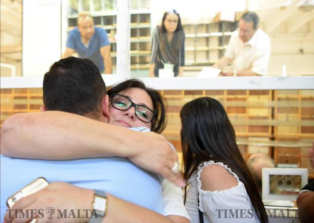Outgoing Parliamentary secretary Deborah Schembri hugs newly elected member of parliament Clayton Bartolo after she lost to him with a mere 15 votes in a casual election held at the Naxxar counting hall on June 20. Photo: Mark Zammit Cordina