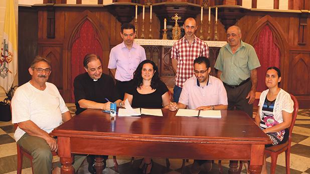 Anthony Galea, Għajnsielem archpriest Frankie Bajada, notary Anna Maria Mizzi, Noel Gallo and Marie Louise Gallo during the signing of the agreement. Looking on are, from left, Lelio Spiteri, Rudy Cauchi and Emanuel Saliba. Photo: Charles Spiteri
