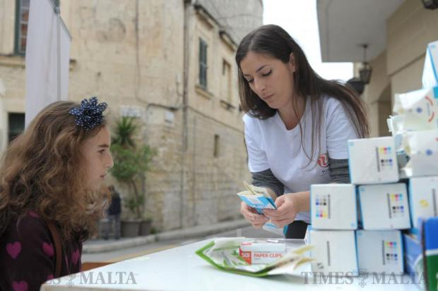 A volunteer shows a young girl how to make a purse from an empty milk carton at the Climate Change awareness raising event in Attard on February 14. The event organised by the Maltese NGO Kopin and the Attard Local Council will was aimed at raising awareness on climate change and related issues. Photo: Matthew Mirabelli