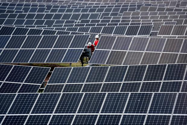 Workers inspect solar panels at a photovoltaic power station on a hill in Linyi.