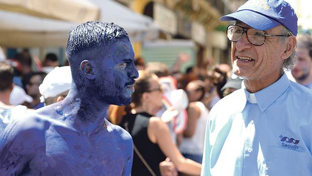 A reveller and a priest at Ħamrun's annual feast of St Cajetan. Photo: Matthew Mirabelli