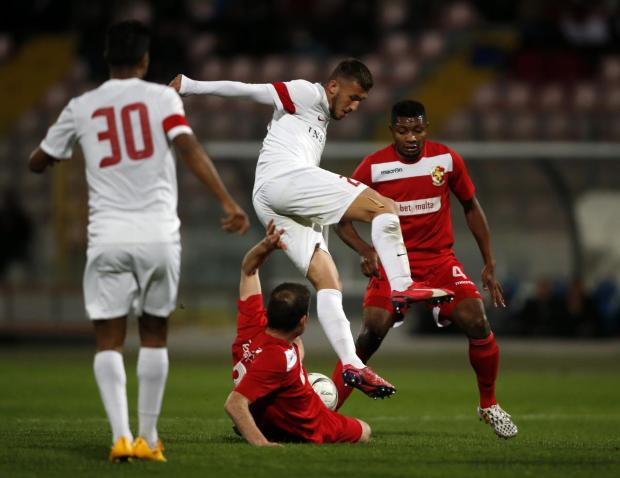 Valletta's Llywelyn Cremona (centre) jumps to avoid the tackle from Naxxar Lions' Andrew Scicluna during their Premier League football match at the National Stadium in Ta' Qali on April 6. Photo: Darrin Zammit Lupi