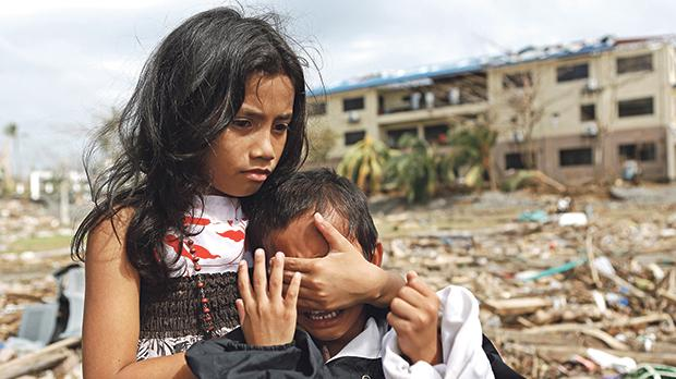 Young survivors of Typhoon Haiyan comfort each other amid the ruins of Tacloban, the Philippines, in November 2013. Photo: Shutterstock