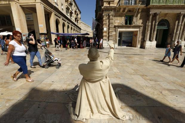 A street performer sits in his spot in Valletta's Republic Street on August 1. Photo: Darrin Zammit Lupi