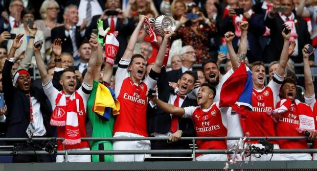 Arsenal's Per Mertesacker and Laurent Koscielny celebrate with the trophy after winning the FA Cup final.