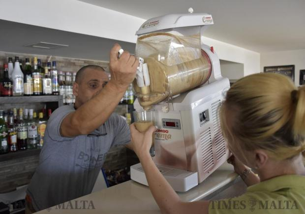 A coffee shop owner tips his iced coffee machine forward to manually pump out the liquid and serve it to his remaining clients after widespread power cuts on August 24. Photo: Mark Zammit Cordina