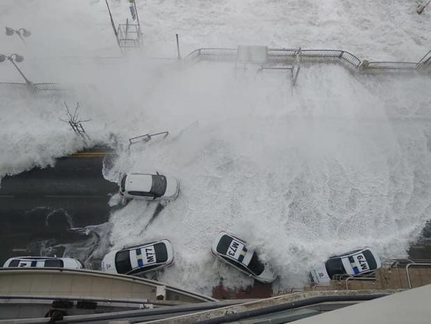 Waves smash into police vehicles along the St Julian's promenade.