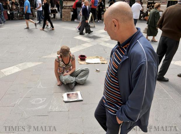 A busker draws a face on the pavement in Valletta on April 20. Photo: Chris Sant Fournier