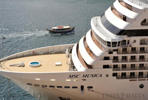 A boat carrying tourists sails past the cruise liner MSC Musica in Grand Harbour on April 20. Photo: Chris Sant Fournier