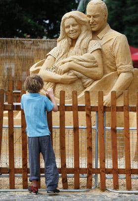 A boy looks at a giant sand castle depicting Britian's Prince William, and his wife Catherine, Duchess of Cambridge holding their son Prince George, on display in London. Photo: Suzanne Plunkett/Reuters