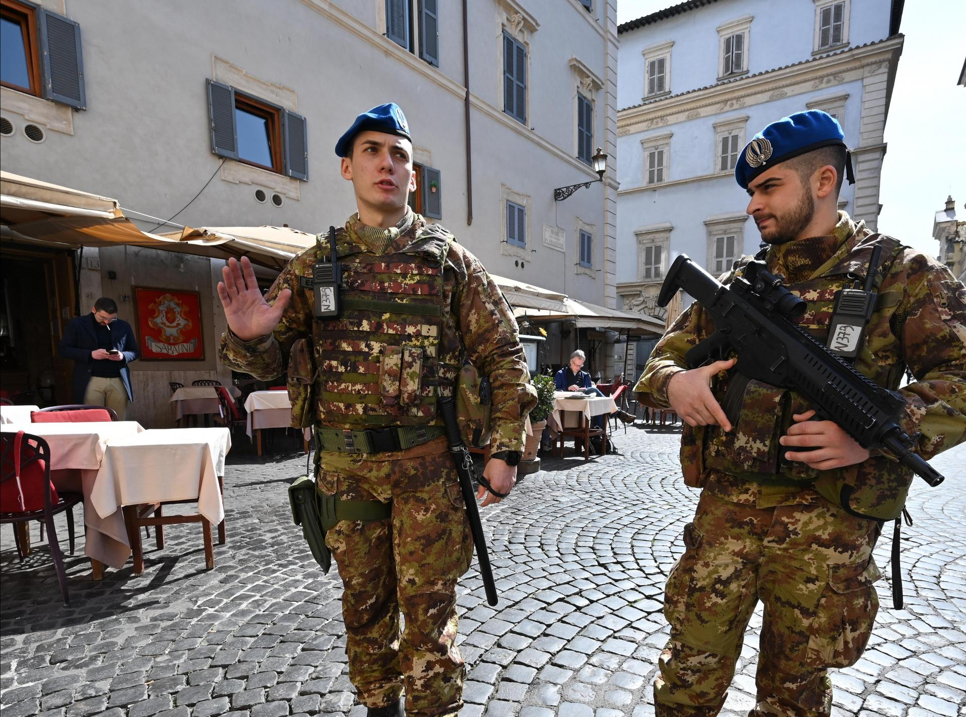 Soldiers patrol past an empty restaurant in the Trastevere district of Rome. Photo: AFP