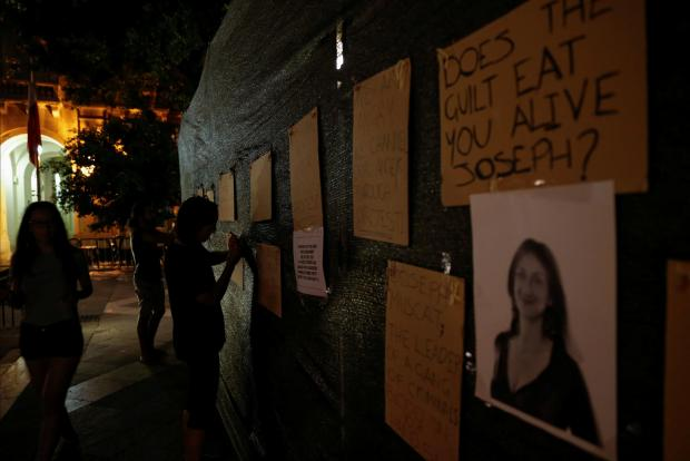 Posters put up by activists on hoarding at the Great Siege monument. Photo: Darrin Zammit Lupi/Reuters