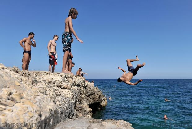 A young man somersaults into the sea from the concrete platform of what used to be the 'Chalet' in Sliema on August 10. Photo: Chris Sant Fournier