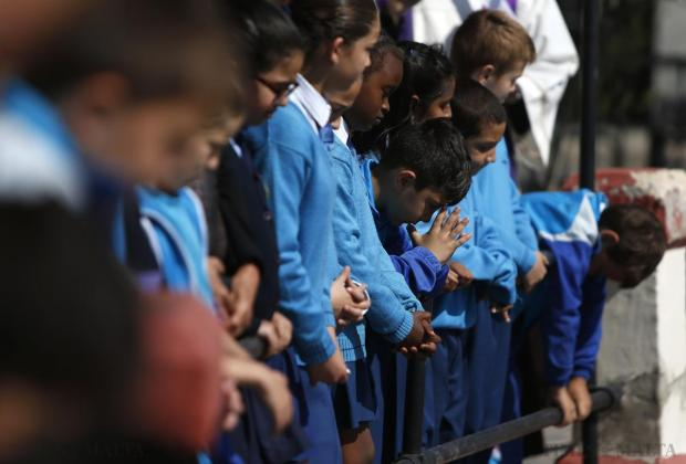 Schoolchildren from St Theresa College Primary School pray after throwing flowers into the sea during a memorial service for migrant victims in Msida on April 22. Photo: Darrin Zammit Lupi