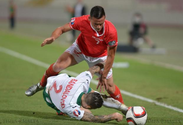 Malta's Clayton Failla (top) vies for the ball as Bulgaria's Ivan Bandalovski goes down during their 2016 UEFA European Championship qualifying match at the National Stadium in Ta'Qali on June 12. Photo: Matthew Mirabelli