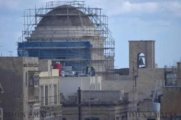 Two construction workers stand dangerously close to the edge of a roof as they work on a building in Valletta on January 18. Photo: Mark Zammit Cordina