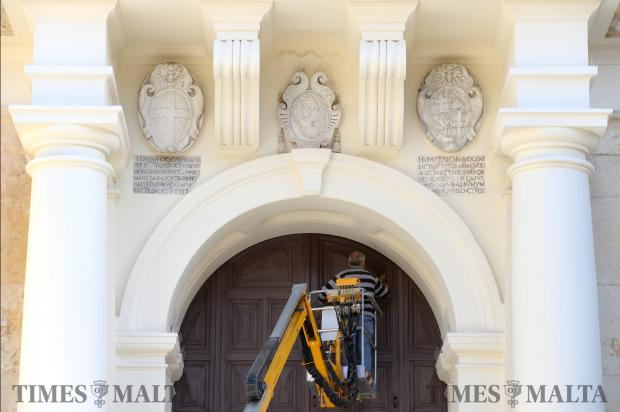 A man cleans the main door of St John's Co Cathedral in Valletta on November 7. Photo: Matthew Mirabelli
