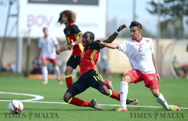 Belgium's Sekou Sidibe, (left) is brought down by Malta's Liam McKay during their UEFA U17 Championship at the Centenary Stadium in Ta'Qali on October 26. Photo: Matthew Mirabelli