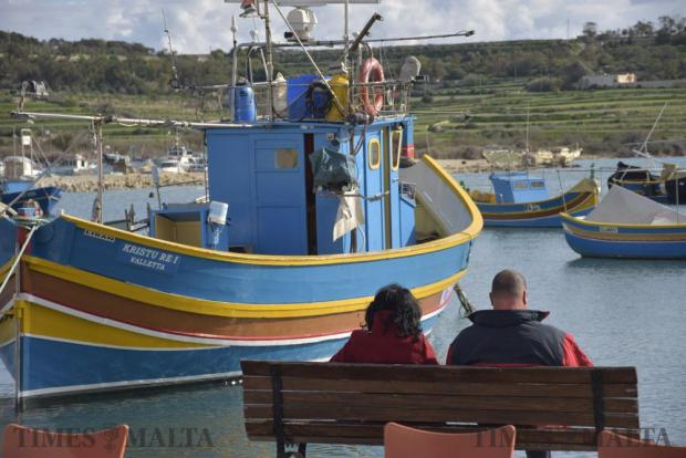 A couple take a moment to sit on a bench in Marsaxlokk, with the view of a traditional Maltese fishing boat on January 10. Photo: Mark Zammit Cordina