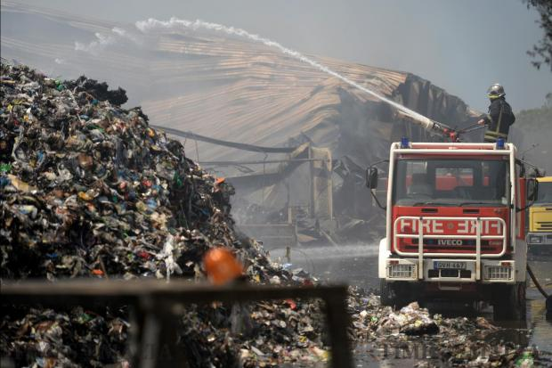 A fire-fighter sprays water onto smouldering piles of waste on May 23, 24 hours after a fire started in the sorting plant at the Sant Antnin recycling plant in Marsascala. Photo: Matthew Mirabelli