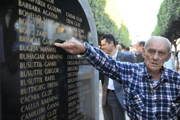 A 'soldier of steel' points to his name on a monument in Paola Square, unveiled by the General Workers' Union on April 28. Photo: Jason Borg