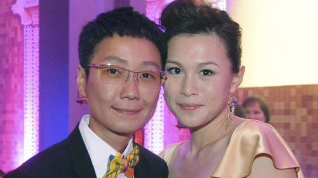 In this undated photo, Gigi Chao, right, daughter of the Hong Kong property tycoon Cecil Chao, poses with her partner Sean Eav at an event in Hong Kong. The daughter of the prominent Hong Kong tycoon who has offered €50 million to any man who can woo her away from her lesbian partner says she's not upset with her father.