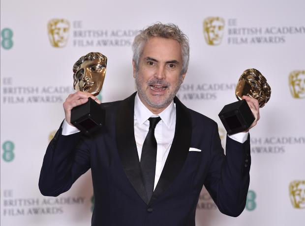 Mexican director Alfonso Cuaron poses with the awards for a Director and for Best Film for 'Roma'.