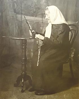 Francesca Teresa Parlar meditating on the Holy Crucifix with rosary beads in hand.